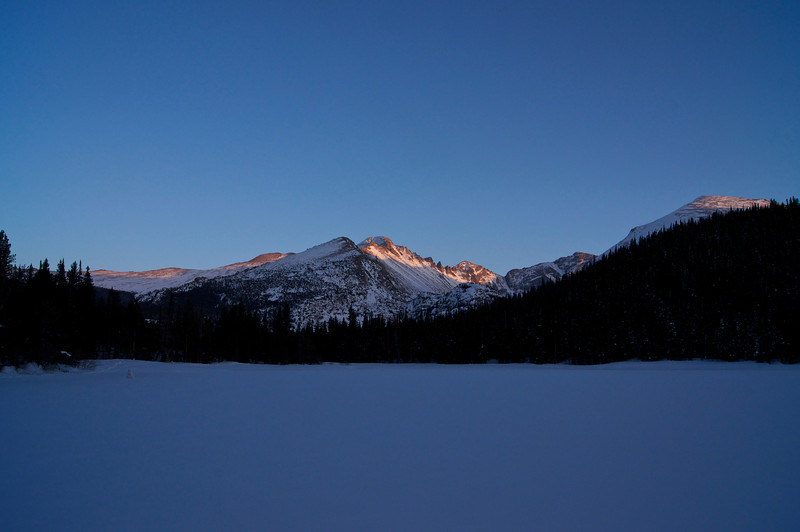 The setting sun casts its last light on Longs Peak.  Viewed from the frozen surface of Bear Lake; Rocky Mountain National Park, Colorado.