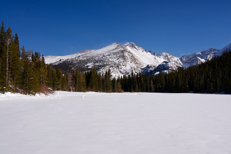 Longs Peak rises over frozen Bear Lake in early spring; Rocky Mountain National Park, Colorado.
