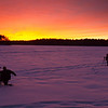 Deuce<br /> Tim and Denise take advantage of a glorious sunset from the ice of a frozen Lake Massabesic.  Well, at least Denise does.<br /> January 2010<br /> I didn't do anything to the colors in post.  This is how it looked.  Most spectacular sunset I've seen yet.