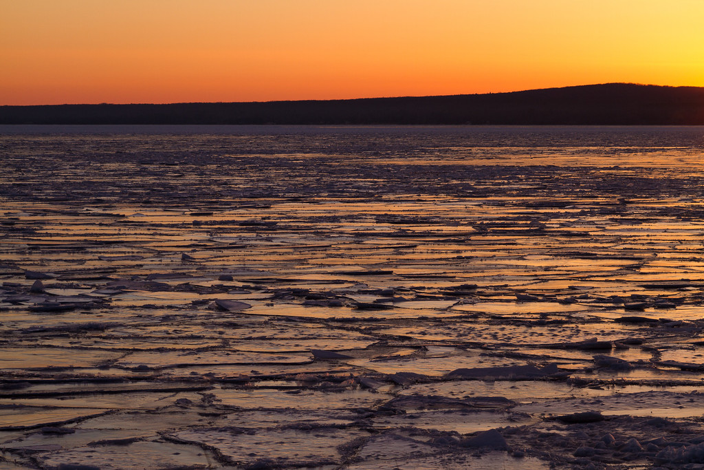 Cracked ice stretches across Keweenaw Bay during a winter sunrise.