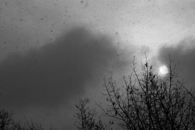 The early morning sun is captured peeking from the clouds of a snow squall.  (B/W)