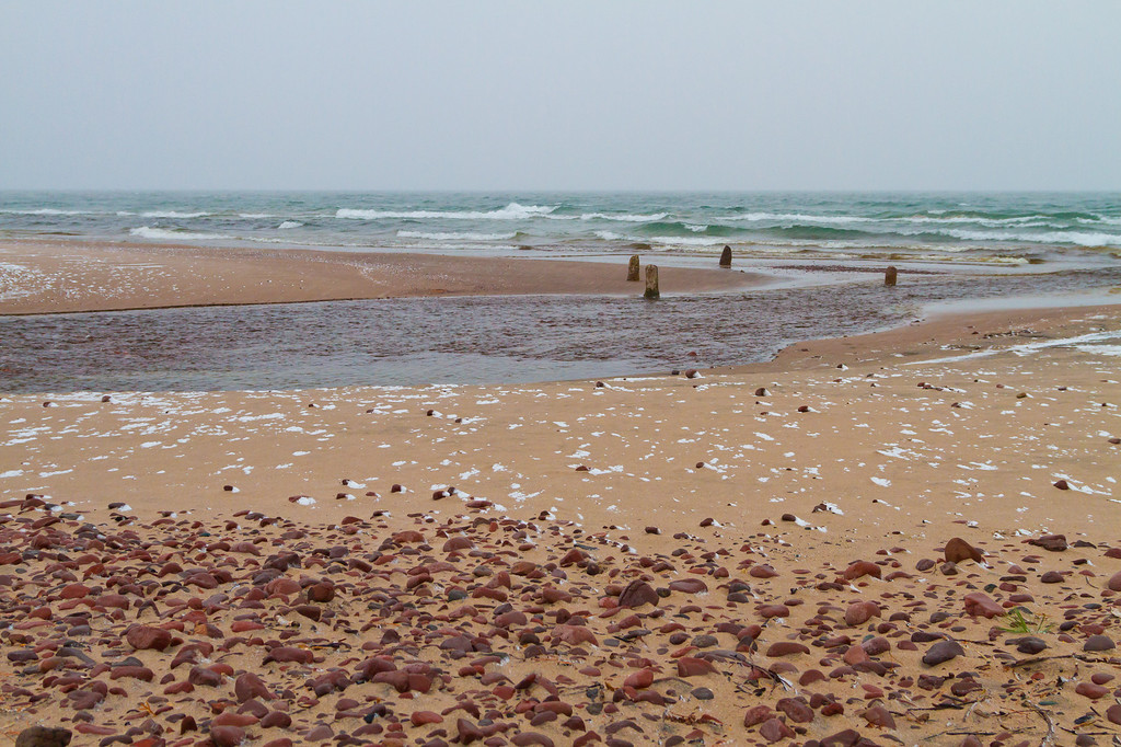 Waves, sand, rocks and snow surround the remnants of a pier in Eagle River MI.