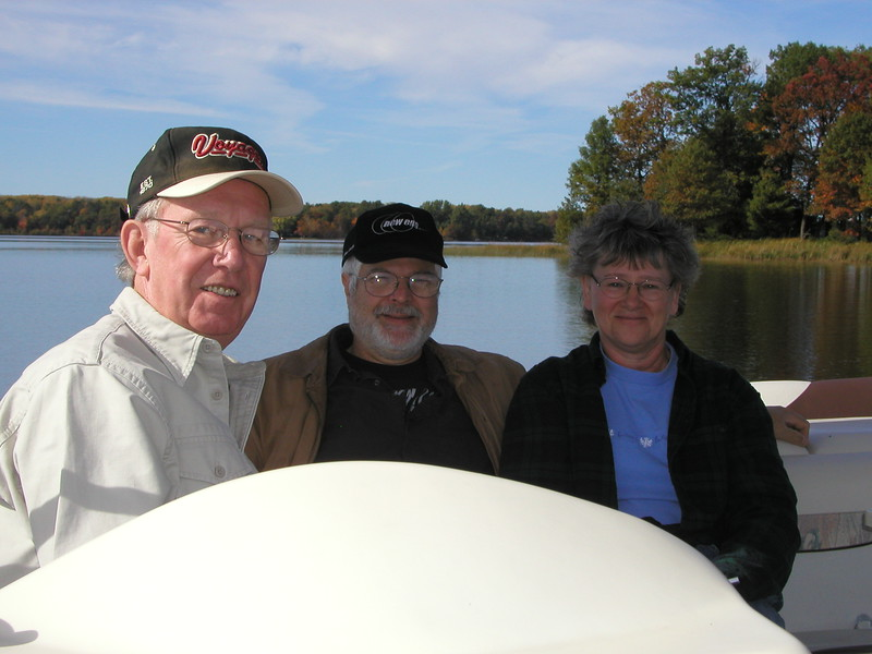Gene (center) show friends Walt & Cathy the beauty of the lake on a pontoon tour.