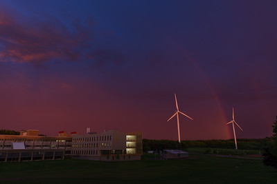 A vivid sky and double rainbow manifests itself behind the wind turbines and brand new Asquino Science Center at Mount Wachusett Community College In Gardner Massachusetts.