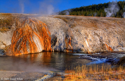 Colorful runoff from springs in the Upper Geyser basin. The Firehole River is in the foreground.