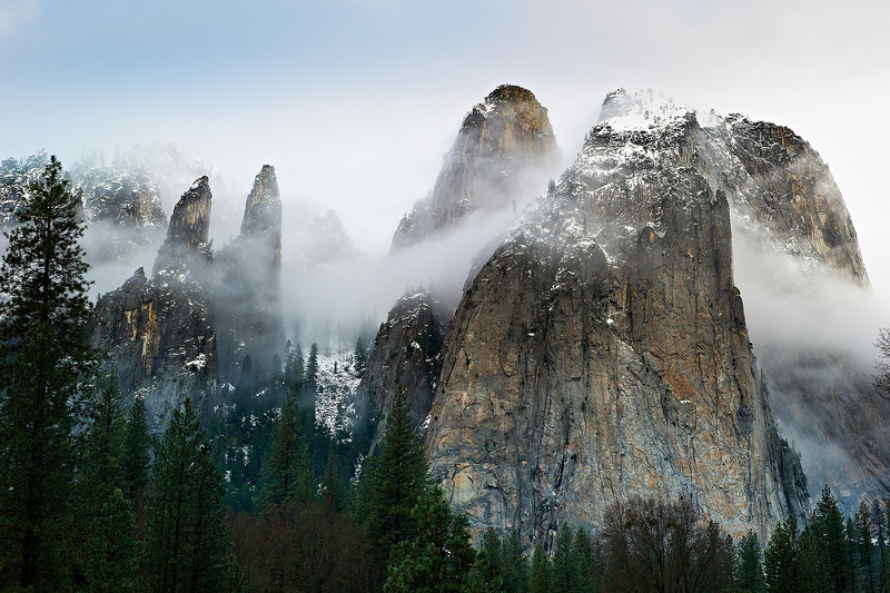 """""""Cathedral Spires and Rocks in Winter"""". Just back from another fantastic weekend in Yosemite including the Yosemite Renaissance reception! I did get out to take pictures in between the bad weather. This morning was perfect...the clouds and fog were swirling around the spires and rocks here with a hint of blue sky peeking through! The two spires on the left, I believe, are called the Lower and Higher Cathedral Spire, while the the two on the right are the Higher Cathedral and Middle Cathedral Rock. I can just imagine seeing the climbers ascending those later this Spring."""
