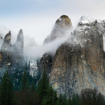 """Cathedral Spires and Rocks in Winter"". Just back from another fantastic weekend in Yosemite including the Yosemite Renaissance reception! I did get out to take pictures in between the bad weather. This morning was perfect...the clouds and fog were swirling around the spires and rocks here with a hint of blue sky peeking through! The two spires on the left, I believe, are called the Lower and Higher Cathedral Spire, while the the two on the right are the Higher Cathedral and Middle Cathedral Rock. I can just imagine seeing the climbers ascending those later this Spring."