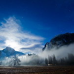 """""""Full Moon Rising over Half Dome"""" The clouds and fog were pretty thick along the ground as we were coming back from a day of shooting. The full moon was rising behind Half Dome and created an ominous glow with the clouds. For the photo techies... I captured this with the Nikon D3S @12,800 ISO, f/8 and 4s and the 14-24 lens that I rented for the last trip. Sure would LOVE to own this camera, but at $5200 for the body and $1800 for the lens, I am going to have to wait a while. Pretty amazing to push something to that ISO! I DID run this through two passes of a noise filter (Noiseware Pro) in Photoshop"""