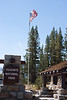 A stiff breeze stiffens the flag over the ranger station at the entrance to Yosemite.