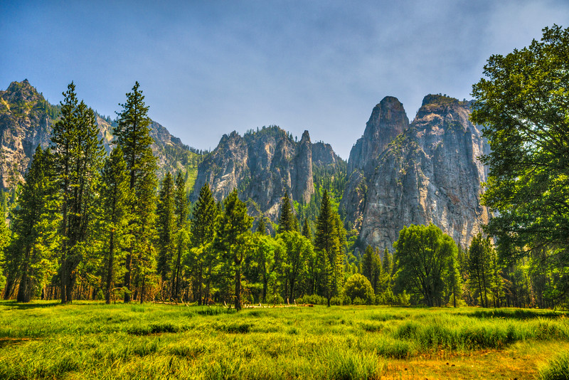 """Cathedral Rocks and Spires in Summer"" in Yosemite National Park.   Driving along the valley floor in summer might bring visions of thousands of visitors to some... but there are still those places where not a single person can be seen!  This is Cathedral Rocks and Spires and this clearing is an easy pull-out along the Northside drive.  A perfect spot for a picnic!  Rock climbers enjoy these rock to climb!  I believe Lower and Higher Cathedral Spires are there in the center while Higher and Middle Cathedral Rock are on the right.  Spires Gully is in the middle between the Cathedral Spires and Rocks.  There is a climbing route along there aptly named ""The Crucifix"" that sounds like fun (you can see info on that 5.12b climb here - <a href=""http://www.mountainproject.com/v/the-crucifix/106140318"">http://www.mountainproject.com/v/the-crucifix/106140318</a>)  Feel free to share the image and + it if you enjoy it!  <br /> Copyright John Harrison Photography"
