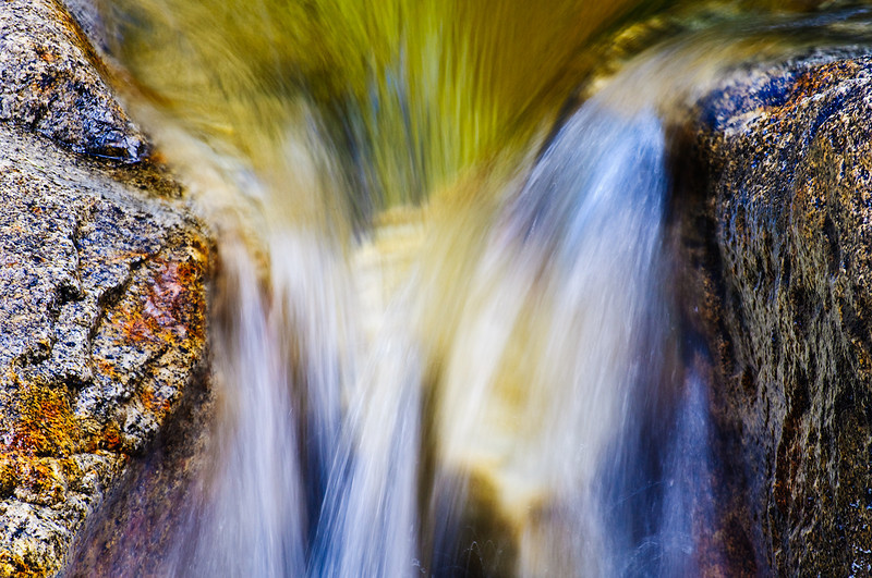"""""""Spring Reflections on the Merced"""",  """"Water, Light and Textures"""" series.  Yosemite National Park.  This was a hidden gem - just a simple flow coming down the Merced river between two rocks.  The green reflections of the trees and the soothing water streaming by.  The orange and blacks specs on the rocks caught my eye.  I didn't see the blue specs in the rocks until I looked more closely at the image. This was shot during the Aperture Nature Photography Workshop Contest trip to Yosemite in January 2009."""