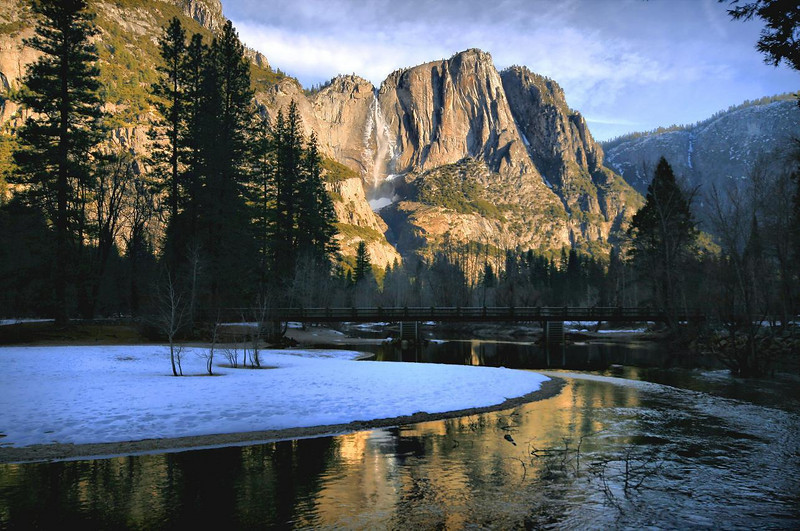 A shallow and faster moving section of the Merced River reflects the morning glow from Upper Yosemite Falls. Mist from the falls freezes overnight on adjacent rocks as it has here, then melts during a warm day. It was unseasonally warm during our visit, creating higher than usual melting and greater flow on the waterfalls. 7:50AM, Feb 14, 2010