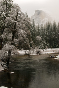 Half dome peaks thru the snow on a wintery day