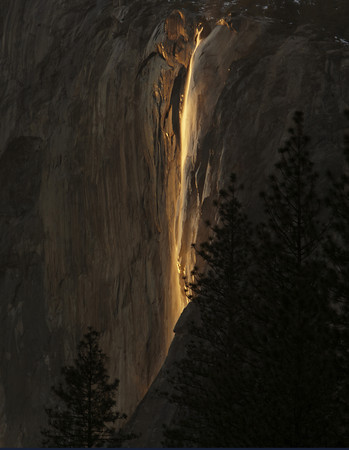 Last Light on Horsetail Fall<br /> <br /> Located in Yosemite National Park.<br /> This is a seasonal water fall that flows in winter and early spring. The fall occurs on the east side of El Capitan. There are a few days every February if the conditions are just right with high water flow and an absence of clouds. This waterfall is lit up by the last light from the setting sun. The mist will also enhance the color with a bright orange glow. In some years, more dramatic images have been made by increased water flow and some wind, Galen Rowell took an iconic image of this fall back in 1974.<br /> <br /> The fall is best seen and photographed from a small clearing close to the picnic area on the north road leading out of Yosemite Valley east of El Capitan.<br /> <br /> This was photographed on the south side from Cathedral Beach with at least 40 Photographers standing tripod to tripod trying to get the best composition...<br /> If you look close you will see the water flowing at the top and an occasional glow around the mist. I keep going back to witness this special event each year.<br /> © Copyright 2011 All Rights Reserved