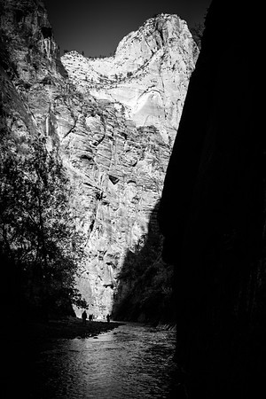 Hikers walking in the Narrows provide perspective for the soaring walls of the Navajo Sandstone.