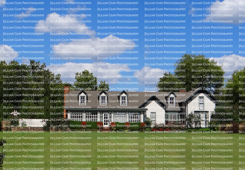 Large plantation home with blue skies and white clouds