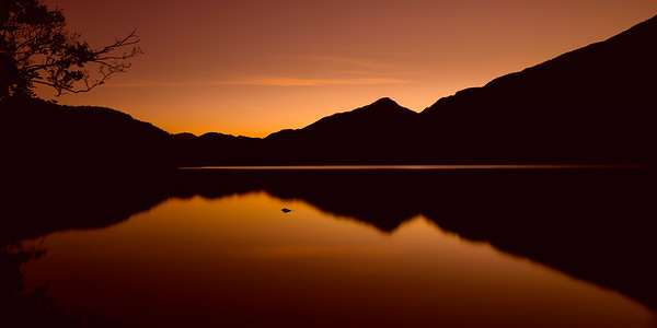 Mountains reflected in Llyn Gwynant under a burnt orange sky