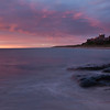 Bamburgh Castle at dawn. This castle is found on the Northumberland coast. The Farne Islands can be seen on the horizon.