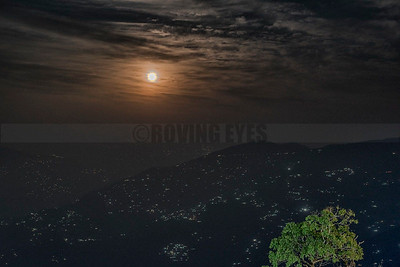A18:The full moon shines through the clouds over Darjeeling in West Bengal,while the city lights sparkle like diamonds in the night.