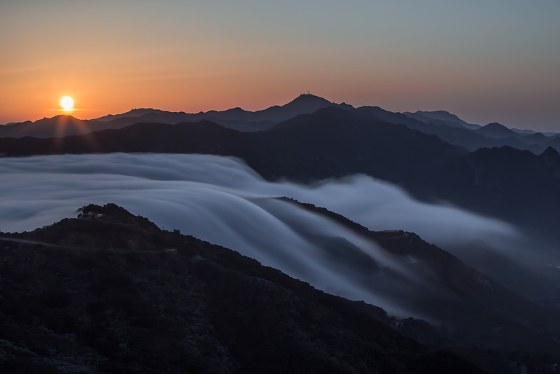 Fog spills over the mountains of Malibu, California.