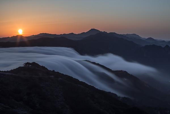 Fog spills over the mountains of Malibu, California.