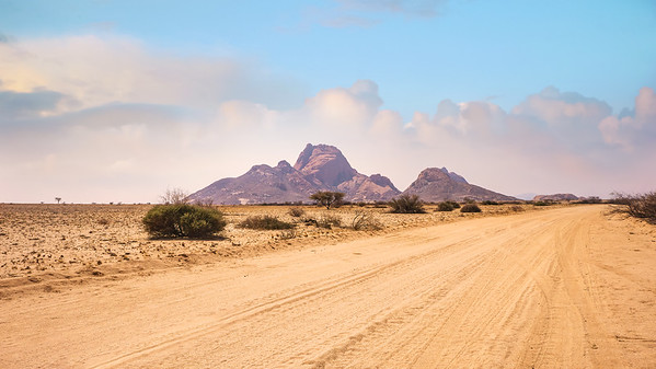 The huge granite peaks of Spitzkoppe, Namibia in the midst of a vast African landscape scene in the Namib Desert.