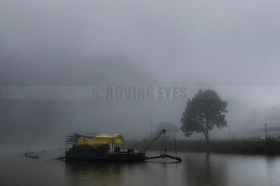 A8:A dredging boat is moored silently in the mist. Lake Sumendu,Mirik,West Bengal