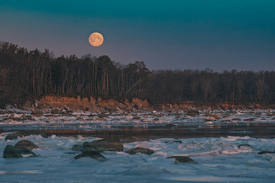 Moonset over seacoast by winter morning