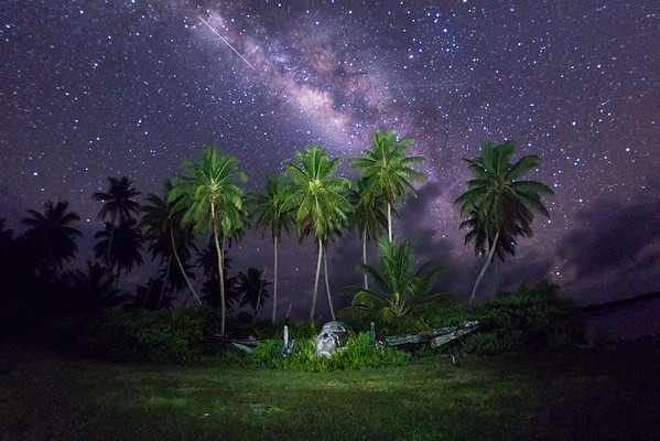 A glimpse of the Perseids meteor shower over a crashed plane on Palmyra Atoll.