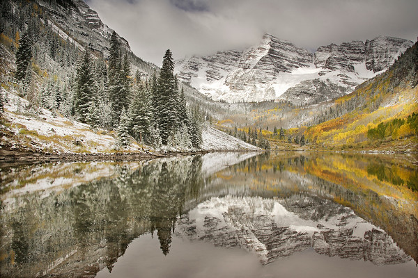 Fresh snow on Maroon Bells and autumn colors reflected in Maroon Lake, White River National Forest, Colorado