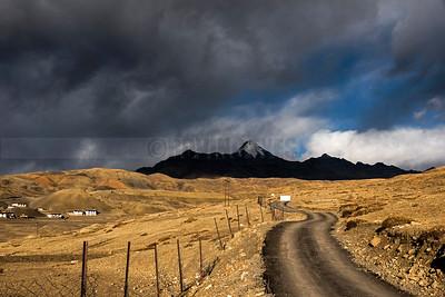 A12:A road snakes in towards Mt. Chau Chau Kang Nilda, Langza, Spiti,Himachal Pradesh,under a sombre sky