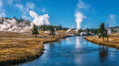 View of the Firehole River flowing through Yellowstone's Upper Geyser Basin, part of the most active geyser field in the world. Old Faithful can be seen erupting in the background.