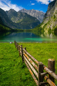 Two travellers sitting near alpine lake with spectacular mountains view