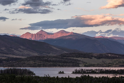 Two Colorado 14ers, Torreys peak and Grays peak, glow red in the setting sun over Lake Dillon.