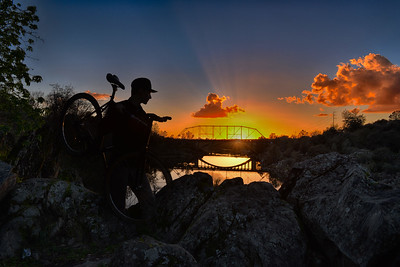 Biker and Sunset Behind Truss/Rainbow bridges
