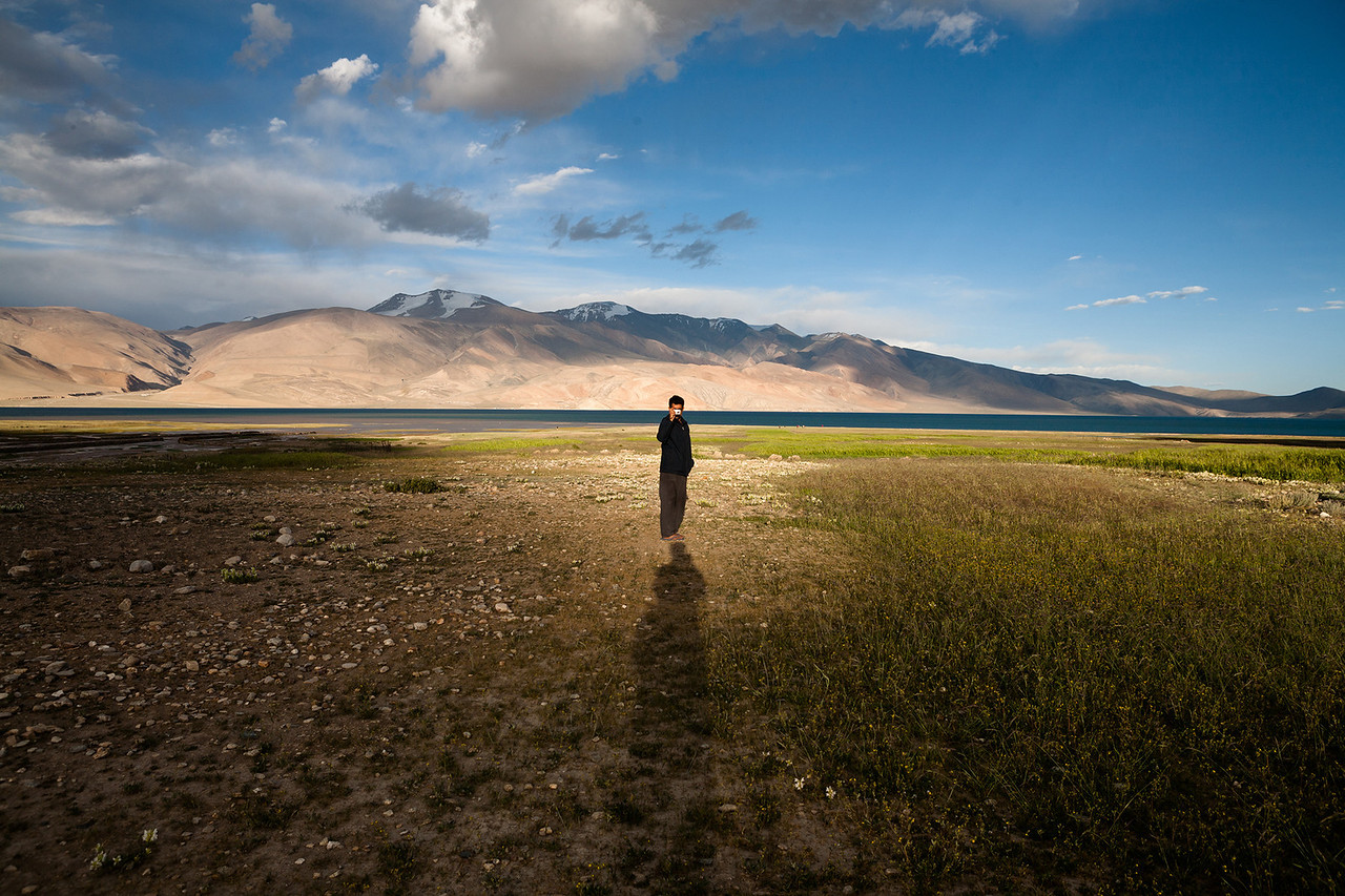 Tso Moriri, at a distance of 250km from Leh is a high mountain lake at a height of around 4500m. We were walking towards Tso Moriri and I saw the concentrated natural light at one place. My friend was standing right in the centre of the light and the sun was about to set. Warm light, long shadows, beautiful Tso Moriri lake in the background created the right moment to take this shot. All I did, was align myself (my shadow) to create a magnificent levitating effect to figure in the centre.