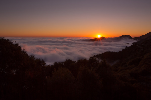 Standing atop Mt. Wilson, the sun sets behind the fog that conceals the city below.