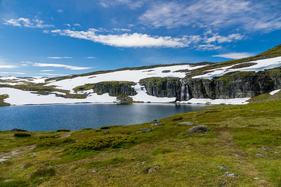 Highland norwegian summer landscape with lake and snow