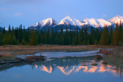 The Mitchell range is reflected in the Kootenay river at dusk. Mt Harkin is on the far right. Kootenay National Park, Canada