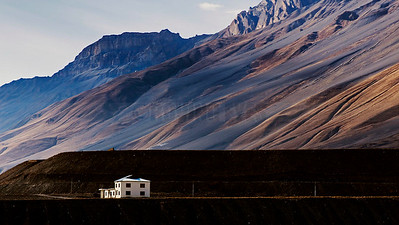 A13:The white house sits in desolation,dwarfed by the towering mountains of Spiti,Himachal Pradesh