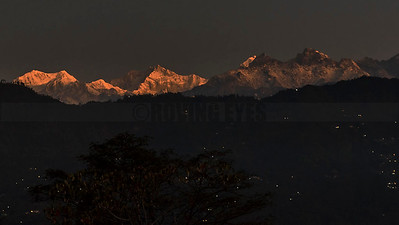 A16:Mt.Khangchendzonga shimmers in the light of dawn,as the night lights still twinkle in the villages,as seen from Bermiok,a small hamlet in West Sikkim