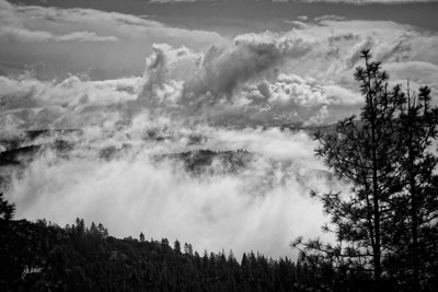 Storm clouds above and clouds/fog/mist rising from the American River Divide.