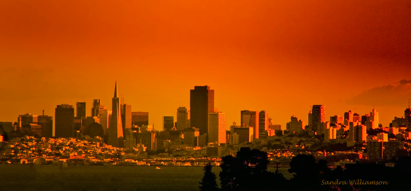 Sunset San Francisco skyline from high hill north along coast.