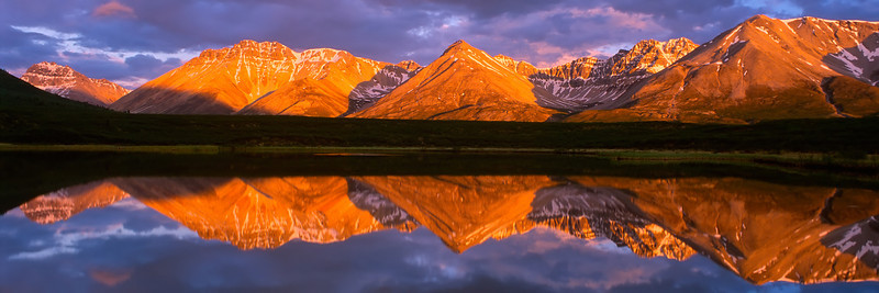 The warm evening light warms the Mackenzie mountains with Alpenglow reflected in a small moose pond, Yukon, Canada