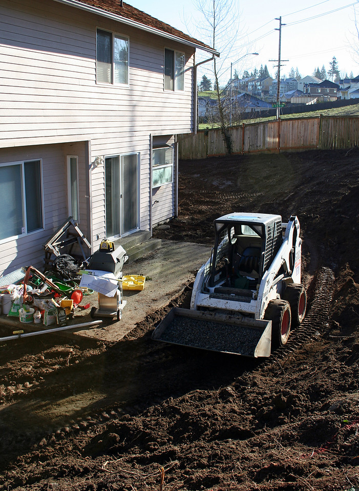 They start to remove the slope behind the house to make more useable space