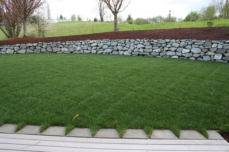 The new grass looks great and is a breeze to mow now that the ground is flat.  Notice how the stone wall integrates into the deck.