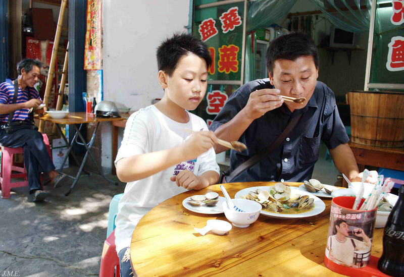 A father and his son enjoy a lunch of clams at a local restaurant.