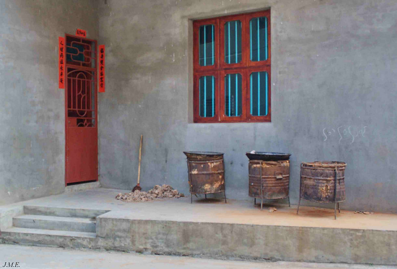 Jingsa Village: Porch showing three portable ceremonial money burning furnances.