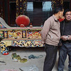 Construction managers consulting in front of altar table in a temple under construction in Hai Yue Village.