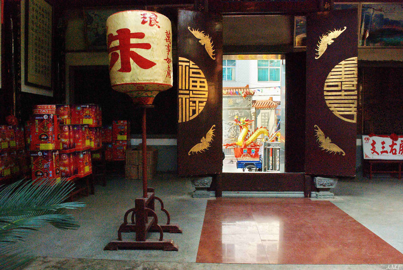Interior view of a temple in Langqi Town with fireworks stacked against the left wall and a golden dragon passing by the front door.